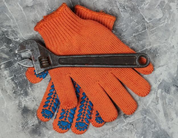 灰色のコンクリートの背景に作業用手袋とレンチ。上面図