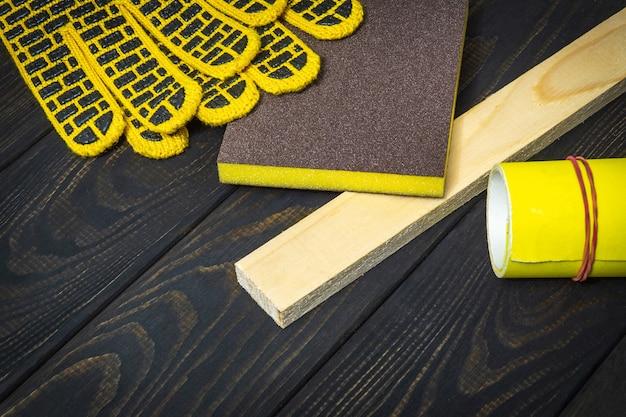 Рабочие перчатки и желтая наждачная бумага для шлифования деревянных досок