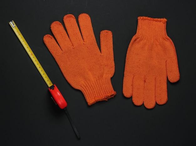 Рабочие перчатки, рулетка на черном фоне. инструменты и инструменты для строительных рабочих, средства безопасности. вид сверху