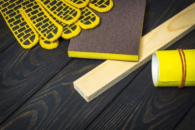 Work gloves and yellow sand paper for sanding wooden boards