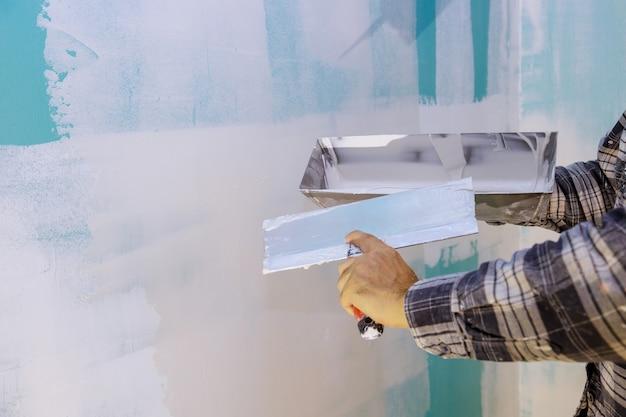 未完成の壁に左官工具を使用して手工具の壁を加工する