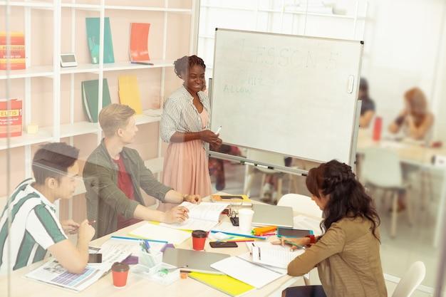 열심히 일하다. 그녀의 학생과 이야기하는 동안 그녀의 얼굴에 미소를 유지하는 귀여운 어두운 피부 여자