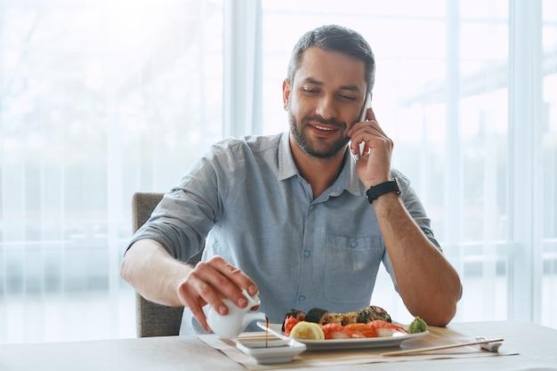 열심히 생각 열심히 먹고 웃으면서 스시를 먹는 잘 생긴 사업가