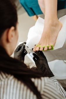 Work hard. top view of dark-haired pedicure master wearing black gloves feeling busy working hard