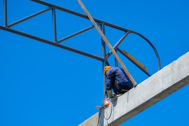Work at height, man welding structure of factory roof in construction site, high risk occupation.