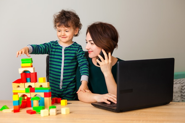 Work at home. a woman sits working on a laptop and talking on the phone, looking at the child as he plays cubes and builds a large multi-story house.