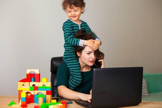 Work at home. a woman with a child sitting on her neck works at a computer and speaks on the phone with the employer while the child plays cubes and hangs around her.
