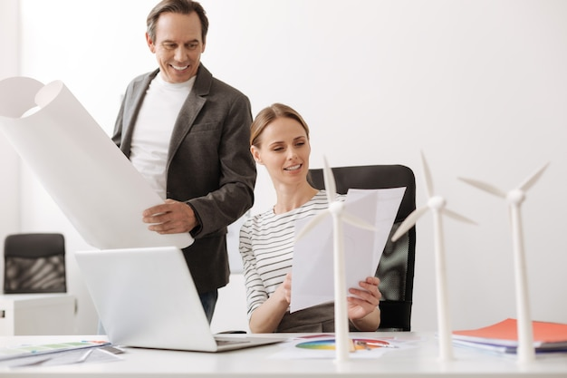 협력하여 일하십시오. 풍력 터빈 프로젝트에서 동료와 함께 작업하는 동안 테이블에 앉아 긍정적 인 여성
