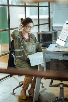 Работа в офисе. беременная женщина в платье цвета хаки чувствует себя занятой во время работы в своем офисе