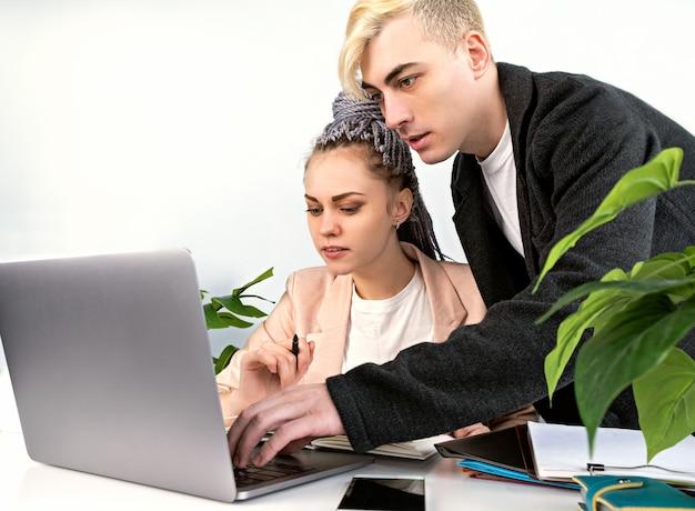 オフィス、ビジネスで働きます。彼の女性の同僚がプロジェクトに対処するのを手伝っている若い魅力的な男性。彼は彼女のラップトップに寄りかかって、女性がテーブルに座っている間、彼女の隣に立っていました。