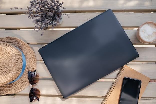 Работайте в свободное время. ноутбук, солнцезащитные очки, ноутбук, телефон и кофе на деревянном столе. вид сверху