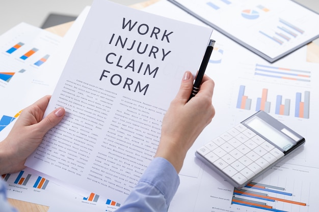 Work injury claim form concept, documents on the desktop