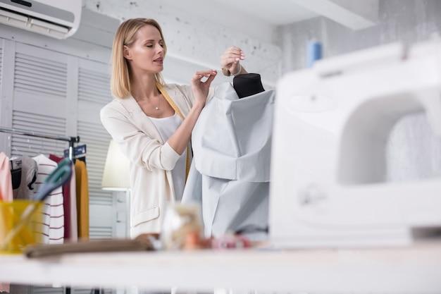 仕事のインスピレーション。見下ろしながらピンを取る魅力的な女性の仕立て屋