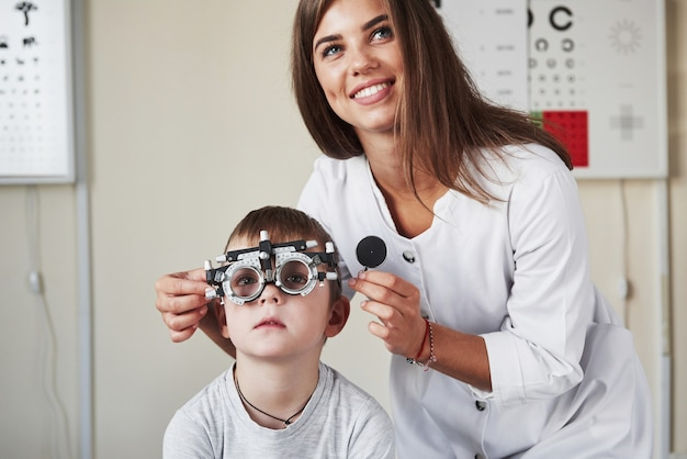 Работа продолжается. врач настраивает фороптер на определение остроты зрения маленького мальчика.