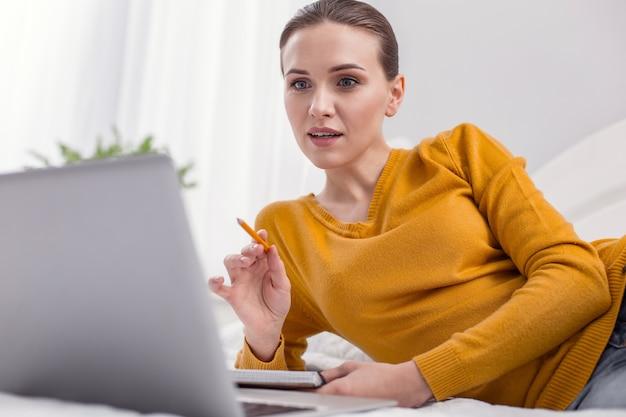 Рабочий вопрос. профессиональная задумчивая женщина-фрилансер открывает рот, работая дома и поднимаясь карандашом