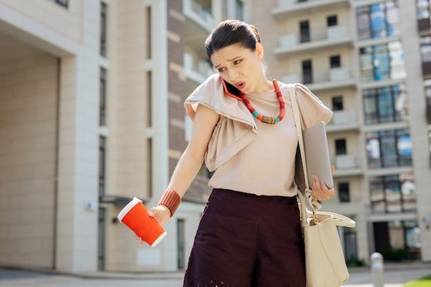 仕事の問題。オフィスを離れる間電話で仕事を議論する美しい感情的な女性