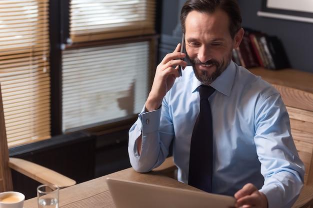 작업 문제. 잘 생긴 열심히 일하는 행복 관리자가 자신의 사무실에 앉아 직장에서 휴대 전화로 말하기