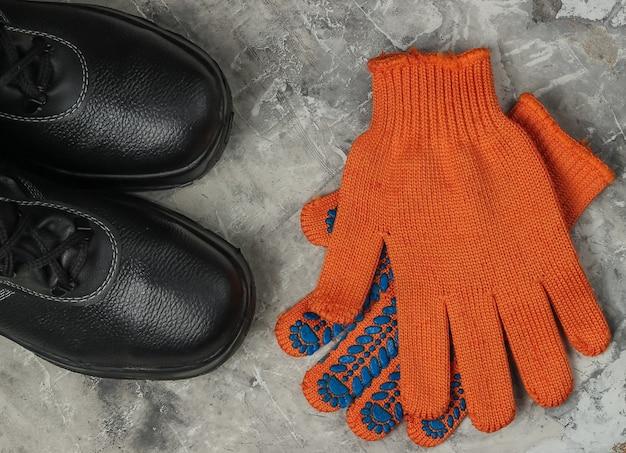 회색 콘크리트 배경에 가죽 신발과 장갑 작업. 안전 장비. 평면도
