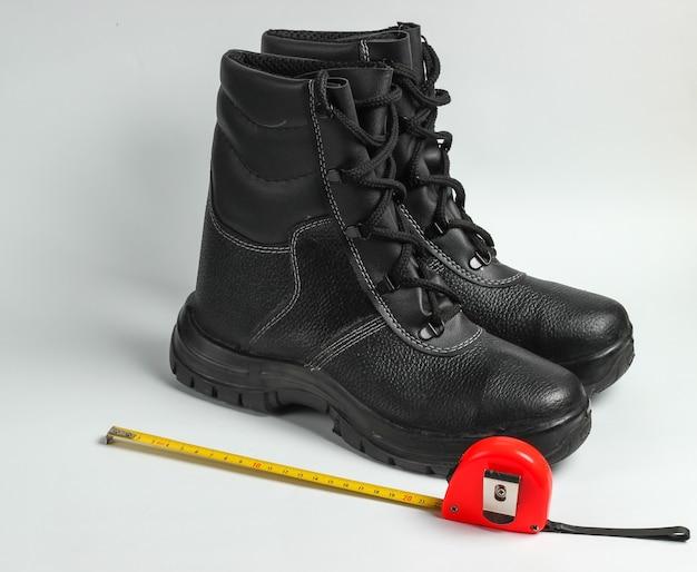 가죽 신발 및 측정 미터 눈금자 흰색 배경에 작동합니다. 안전 장비 및 산업용 도구.