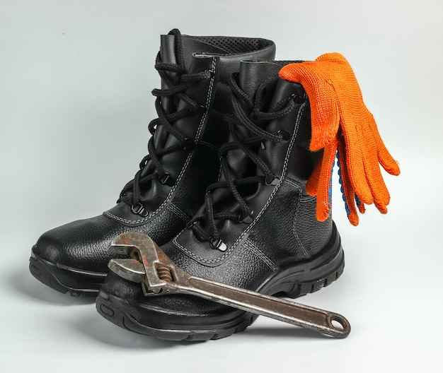 가죽 신발, 장갑, 흰색 바탕에 렌치를 작동합니다. 안전 장비 및 산업용 도구.