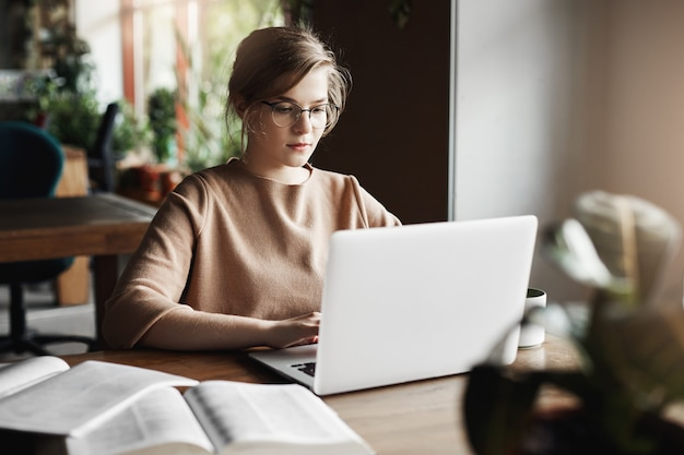 Работа, образ жизни и бизнес-концепция. красивая целеустремленная европейская женщина в модных очках сидит в кафе возле ноутбука, работает над ноутбуком, окружена книгами, делает заметки.