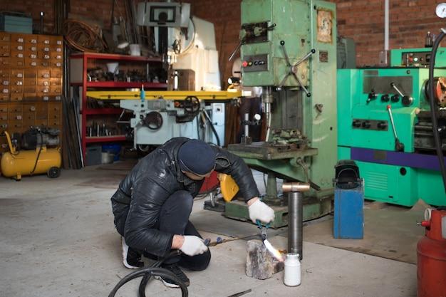 일하는 사람은 마스크의 용접기, 가정 차고의 금속 제품, 화염 연소 가스 용접