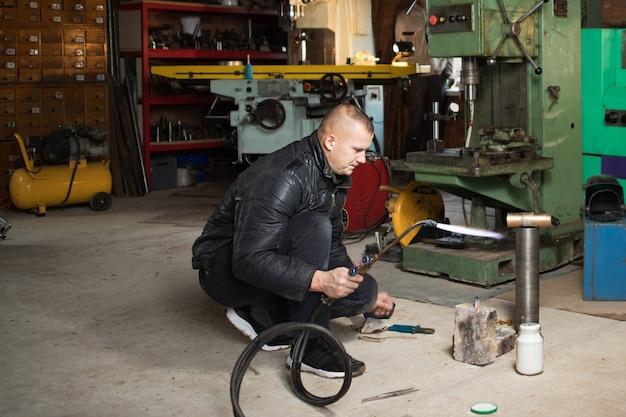Рабочий человек - сварщик в маске, металлическое изделие в домашнем гараже, с газовой сваркой пламенем