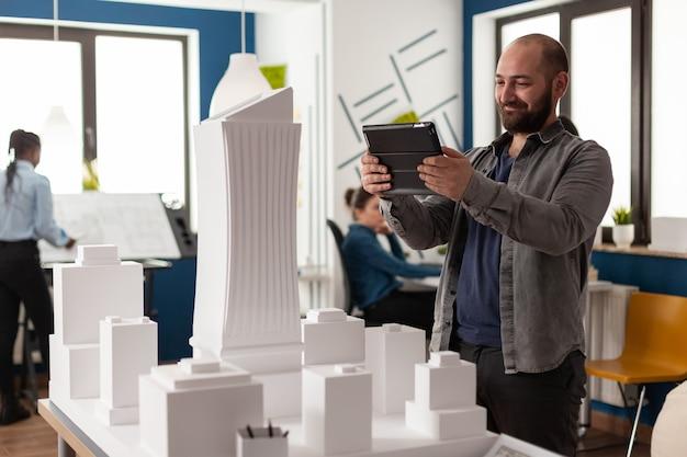建築事務所でタブレットを見ているワークマネージャーの男