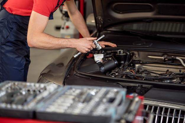 仕事の瞬間。ワークショップで車のオープンフードで働くオーバーオールの経験豊富な男性の自動車修理工の手