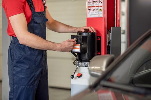 仕事の瞬間。自動車修理店で車の近くのデバイスのスタートボタンを押す男性の手