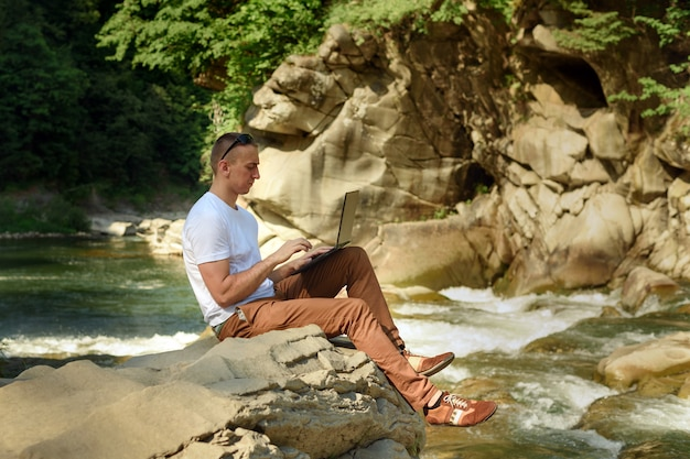 Work in nature concept. man with notebook sitting at the bank of river over the waterfall and green trees. side view