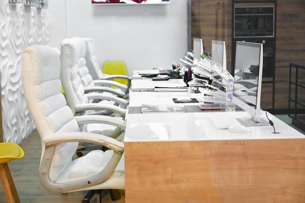 Офисное современное место с компьютерами и мебелью.