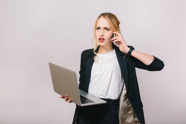 Время работы в офисе занятой молодой женщины в формальной одежде с ноутбуком, разговаривает по телефону. расстроенное настроение, удивлен, работа, профессия, секретарь, офисный работник