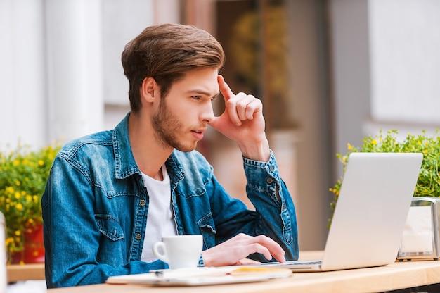 이동 중에도 작업하세요. 노천 카페에 앉아 노트북 작업을 하는 집중된 청년