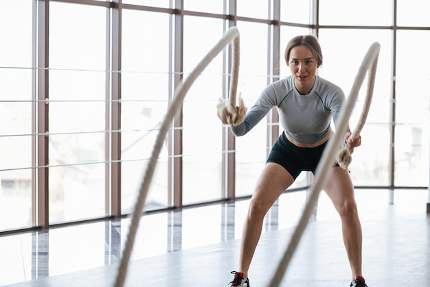 Work out in club near windows. sportive young woman have fitness day in the gym at morning time