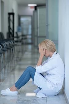 작업 과부하. 그녀의 얼굴을 덮고 바닥에 앉아 피곤 된 금발 여성 의사