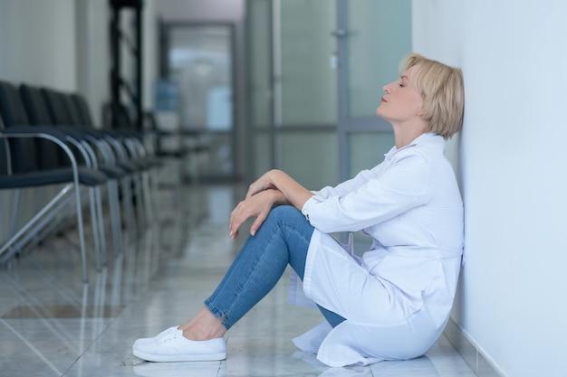 仕事の過負荷。床に座って、壁にもたれて疲れた金髪の女性医師