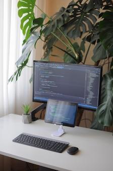 Рабочее место разработчика, экран и планшет с кодом. комфортная работа с растениями из дома