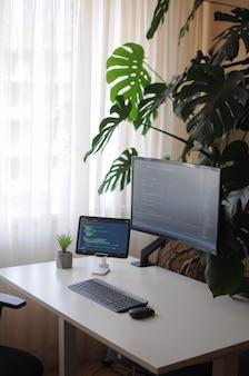 Рабочее место разработчика с изогнутым экраном и планшетом. комфортная работа из дома с растениями.