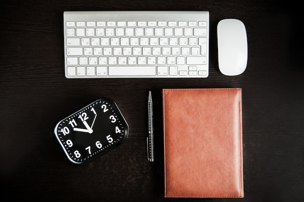 Work place. keyboard, clock, mouse, book and pen on wooden table