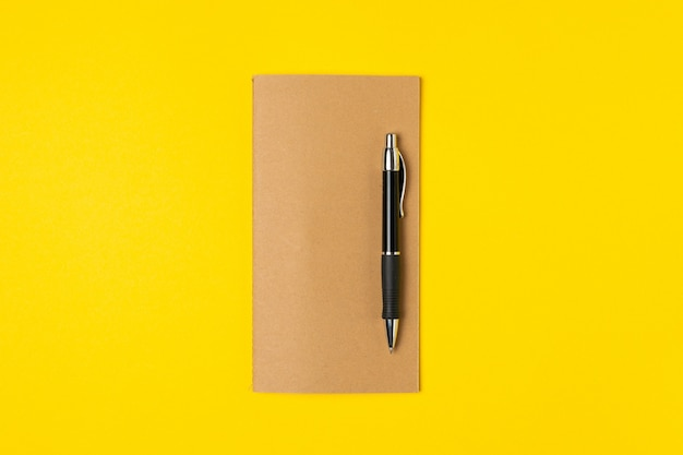 Work place, notepad and pen on bright yellow