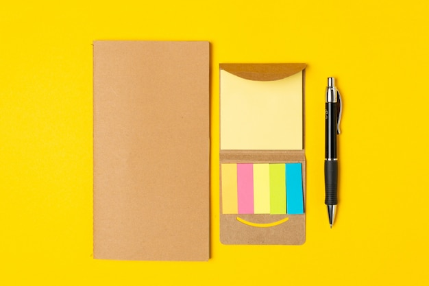 Work place, notepad, sticky notes and pen on bright yellow