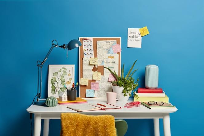 学生の職場。ランプ付きのデスクトップ、開いたノートブック、文房具、緑の屋内植物、青のコーヒー付箋のマグカップ。ホームオフィス