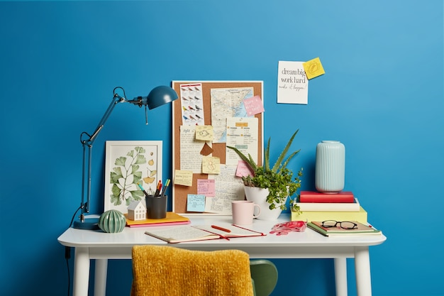 Work place of student. desktop with lamp, opened notebook, stationery and green indoor plant, mug of coffee sticky notes on blue. home office