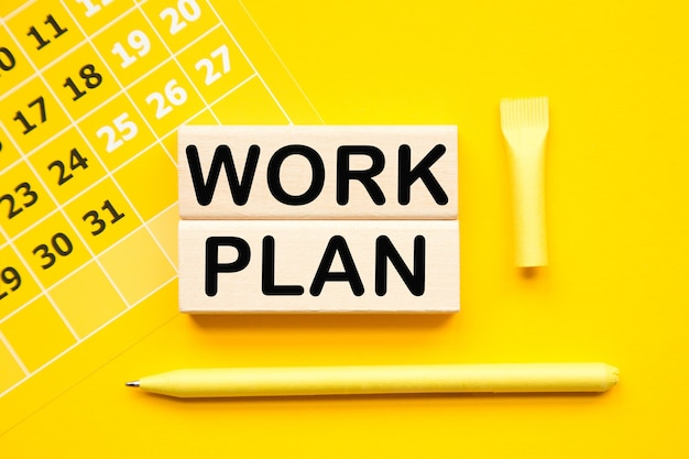 Work plan. calendar and wooden bars with informationon on the a yellow background desktop .