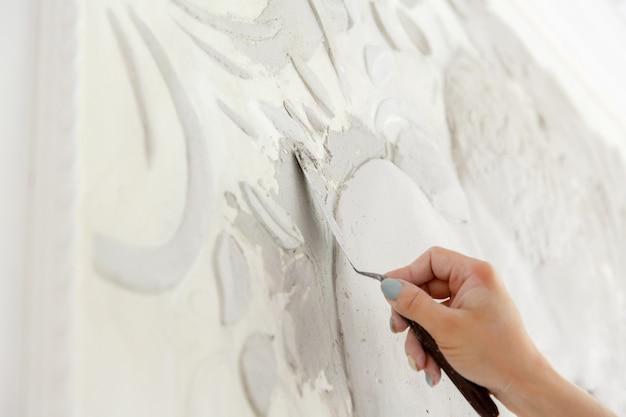 Рабочий процесс женщина кладет раствор шпатлевки на стену с барельефом