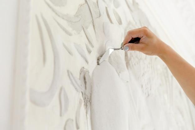 작업 과정 여성 노동자는 basrelief와 함께 벽에 퍼티 솔루션을 넣습니다