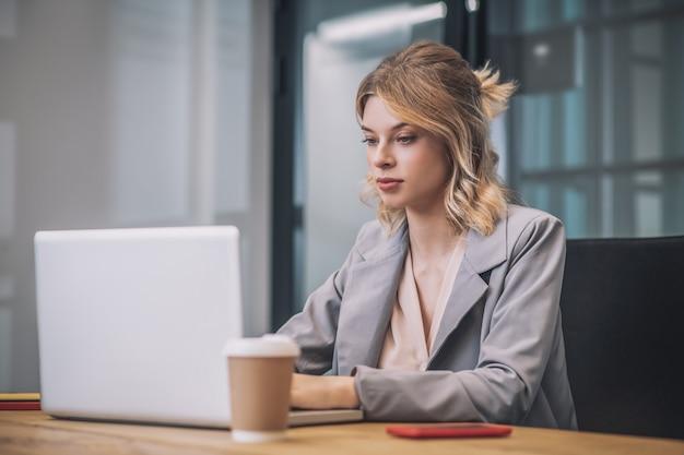 作業過程。明るいオフィスのラップトップで働く灰色のスーツの若い自信を持ってビジネスきれいな女性