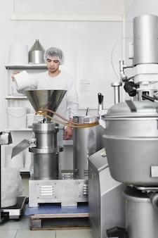 Работа спит кокосовой стружкой в промышленной дробилке - прессе. производство кокосового масла, пасты.