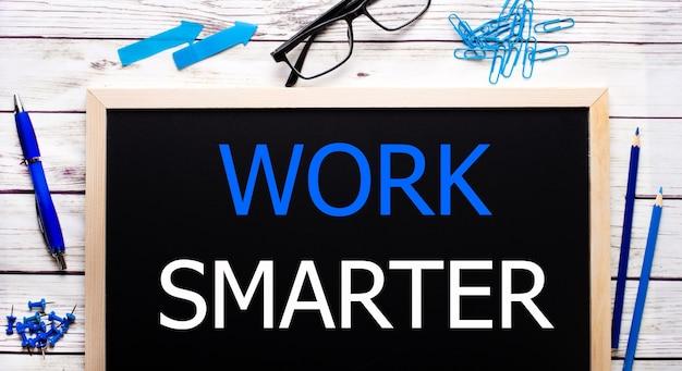 파란색 종이 클립, 연필 및 펜 옆에있는 검은 색 메모판에 더 현명하게 작업하십시오.